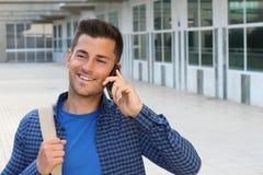 Studente sveglio che chiama dal telefono sulla città universitaria con lo spazio della copia Fotografie Stock