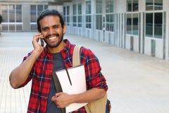 Studente sveglio che chiama dal telefono sulla città universitaria con lo spazio della copia Fotografia Stock
