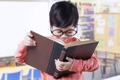 Studente sveglio che sta nella classe mentre libro di lettura Immagine Stock