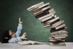Studente sveglio con il mucchio dei libri di caduta Fotografia Stock Libera da Diritti