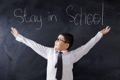 Studente sveglio con testo del soggiorno a scuola Fotografia Stock