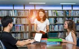 Studente Teenage Talking, libro di lettura, facendo uso del computer portatile Immagine Stock