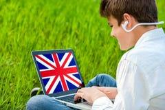 Studente teenager che fa corso inglese sul computer portatile. Fotografia Stock