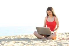 Studente teenager che per mezzo di un computer portatile sulla spiaggia Immagine Stock