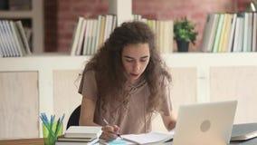 Studente teenager messo a fuoco che studia scrivendo le note che fanno compito di ricerca archivi video