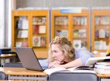 Studente triste con il computer portatile che funziona nella biblioteca Fotografie Stock Libere da Diritti