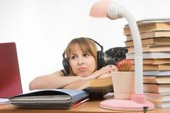Studente triste della ragazza che si siede alle cuffie d'uso della tavola e che ascolta la musica Immagini Stock Libere da Diritti