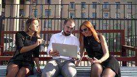 Studente twee en de mannelijke student communiceren op de bank in zonnig weer gebruikend laptop stock video