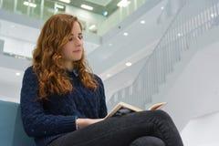 Studente universitario abile Studying in libri moderni bianchi delle biblioteche Fotografie Stock