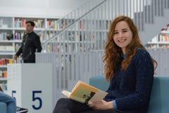 Studente universitario abile Studying in libri moderni bianchi delle biblioteche Immagini Stock