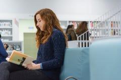 Studente universitario abile Studying in libri moderni bianchi delle biblioteche Immagine Stock