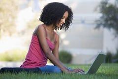 Studente universitario che per mezzo del computer portatile all'esterno Immagine Stock