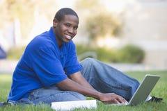 Studente universitario che per mezzo del computer portatile all'esterno Fotografia Stock