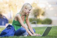 Studente universitario che per mezzo del computer portatile all'esterno Fotografie Stock
