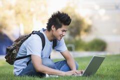 Studente universitario che per mezzo del computer portatile all'esterno Fotografia Stock Libera da Diritti