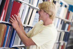 Studente universitario che seleziona libro a partire dalla libreria Fotografie Stock