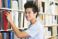 Studente universitario che seleziona libro a partire dalla libreria lei Fotografia Stock Libera da Diritti