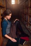 Studente universitario che si siede su un pavimento della biblioteca Fotografie Stock