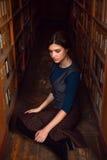 Studente universitario che si siede su un pavimento della biblioteca Fotografia Stock Libera da Diritti