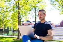 Studente universitario del giovane online che impara tramite computer portatile, sedentesi su un banco su una città universitaria immagini stock libere da diritti