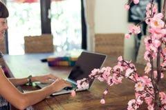 Studente universitario femminile attraente che per mezzo del computer portatile su una tavola di legno Fotografia Stock