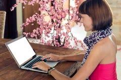 Studente universitario femminile attraente che per mezzo del computer portatile su una tavola di legno Schermo bianco, spazio vuo Fotografia Stock