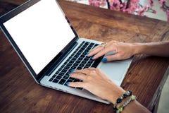 Studente universitario femminile attraente che per mezzo del computer portatile su una tavola di legno Schermo bianco, spazio vuo Fotografie Stock Libere da Diritti