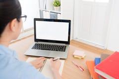 Studente universitario femminile che per mezzo del computer portatile mobile Fotografia Stock