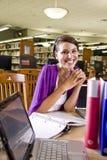 Studente universitario femminile che studia nella libreria Immagini Stock Libere da Diritti