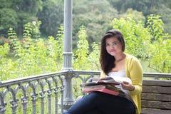 Studente universitario femminile con i libri e gli archivi sul rivestimento in parco Fotografia Stock Libera da Diritti