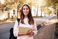 Studente universitario femminile con il libro in città universitaria Fotografie Stock