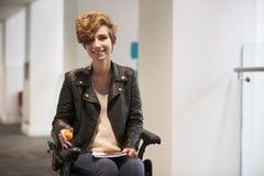 Studente universitario femminile disabile che sorride alla macchina fotografica Immagini Stock