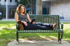 Studente universitario femminile Relaxing On Bench Fotografie Stock Libere da Diritti