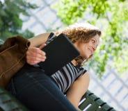 Studente universitario Holding Digital Tablet sul banco Immagine Stock