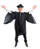 Studente universitario laureato che salta su Immagine Stock