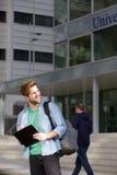Studente universitario maschio felice che sta sulla città universitaria Fotografia Stock