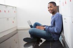 Studente universitario sorridente che per mezzo del computer portatile Immagine Stock