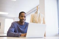 Studente universitario sorridente che per mezzo del computer portatile Fotografia Stock Libera da Diritti