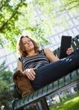 Studente universitario Using Digital Tablet sul banco Fotografia Stock Libera da Diritti