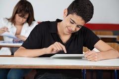 Studente Using Digital Tablet della High School allo scrittorio Fotografie Stock Libere da Diritti