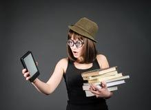Studente in vetri divertenti con i vecchi libri in un mano ed e-lettore in un altro su fondo grigio La ragazza del nerd sta confr Fotografie Stock Libere da Diritti