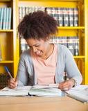 Studente Writing In Book alla biblioteca universitaria Fotografia Stock