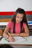 Studente Writing In Book della High School allo scrittorio Fotografia Stock