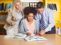 Studente Writing In Book mentre assistenza degli insegnanti Fotografie Stock Libere da Diritti