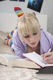 Studente Writing In Book mentre trovandosi sul letto Fotografie Stock