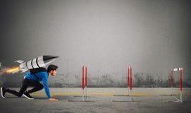 Studenten övervinner hinder av hans studier rusar överst med en raket Arkivfoto