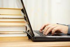 Studenten använder bärbara datorn och bokar för att förbereda sig för examen Arkivfoto