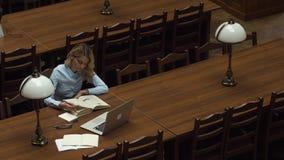 Studenten arbetar med böcker och bärbara datorn i arkivet arkivfilmer