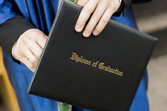Studenten avlägger examen anseende i rad och rymma hans diplom Arkivbild