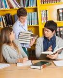 Studenten-Carrying Books While-Freunde, die herein sitzen Lizenzfreies Stockbild